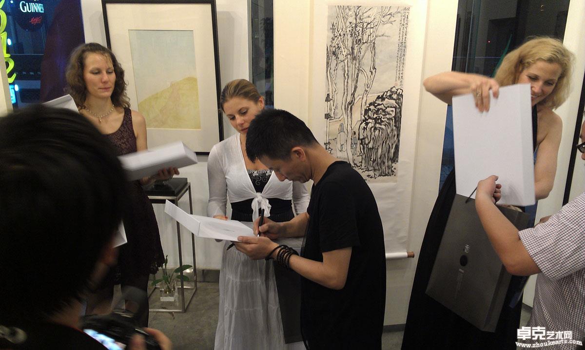 2012年,在画展上为朋友们签名